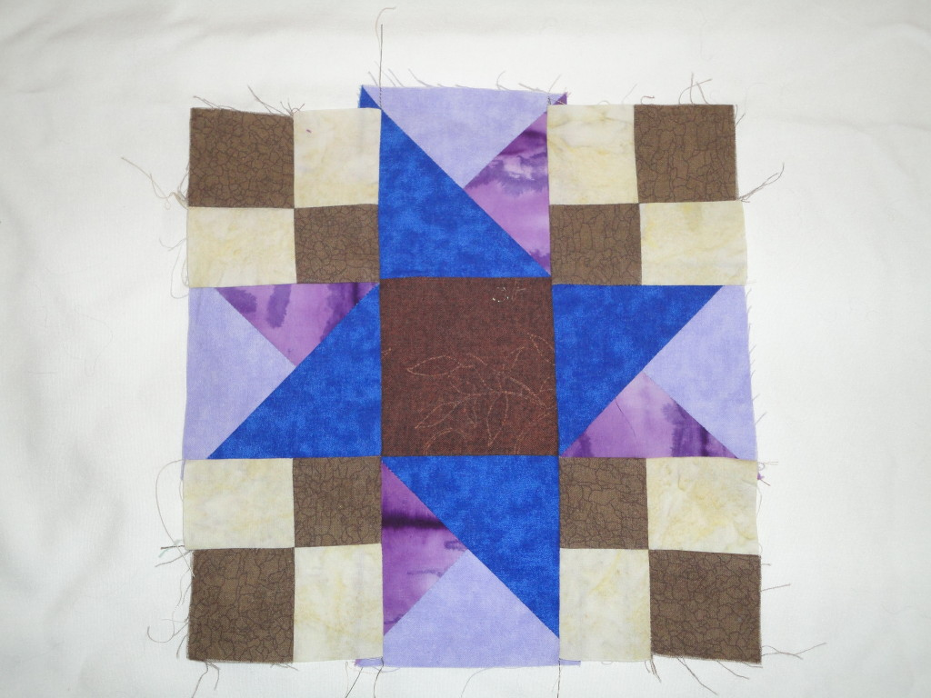 Quilt square in browns and purples.