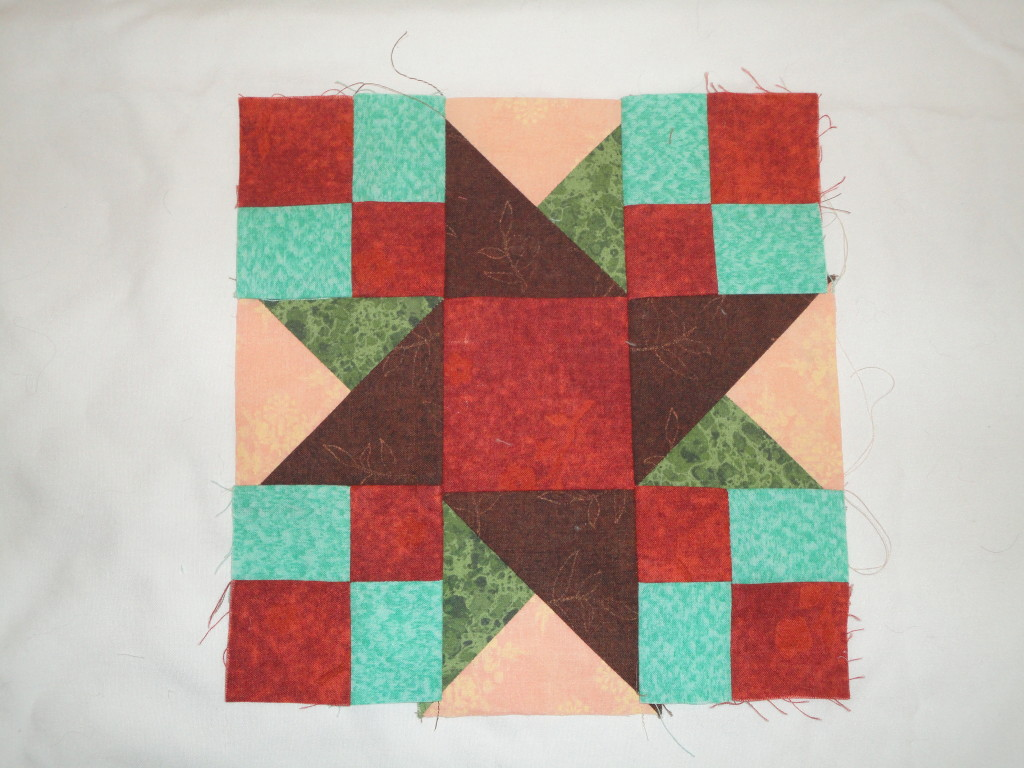 Center quilt block in greens and browns.