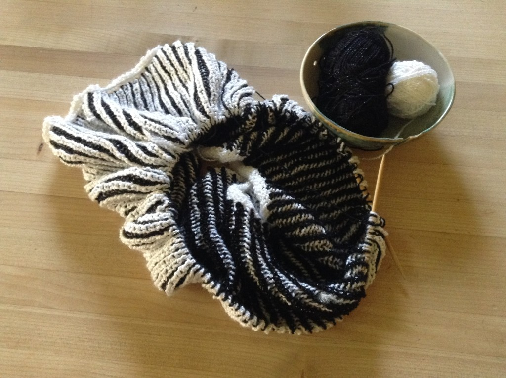 Brioche cowl in black and white with ceramic yarn bowl.